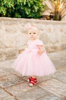 Na jezdni stoi urocza dziewczynka w różowej sneakersowej sukience iz koroną na głowie