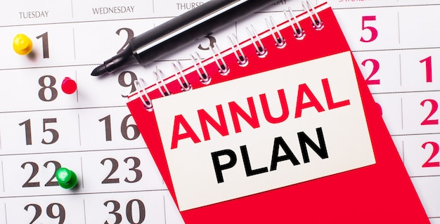 Na kalendarzu biała kartka z napisem plan roczny. w pobliżu znajduje się czerwony notatnik i marker. widok z góry