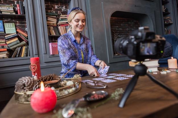 Na kamerze. zachwycona młoda kobieta przepowiadająca przyszłość podczas nagrywania kamerą
