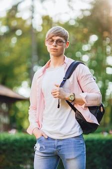 Na kampusie stoi młody przystojny facet w zwykłych ubraniach, okularach przeciwsłonecznych i plecaku