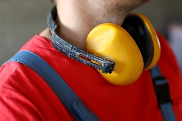 Na karku zawieszono żółte dźwiękoszczelne słuchawki. ochrona słuchu przed głośnymi dźwiękami sprzętu roboczego. są stosowane na budowach, w zakładach produkcyjnych o wysokim poziomie hałasu