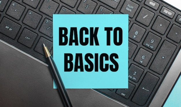 Na klawiaturze komputera znajduje się długopis i niebieska naklejka z napisem back to basics