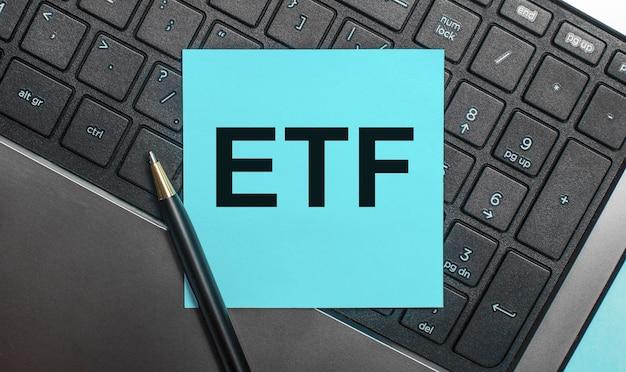 Na klawiaturze komputera znajduje się długopis i niebieska naklejka z napisem etf exchange traded funds. leżał płasko.