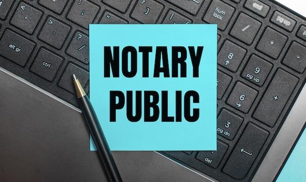 Na klawiaturze komputera znajduje się długopis oraz niebieska naklejka z napisem notary public