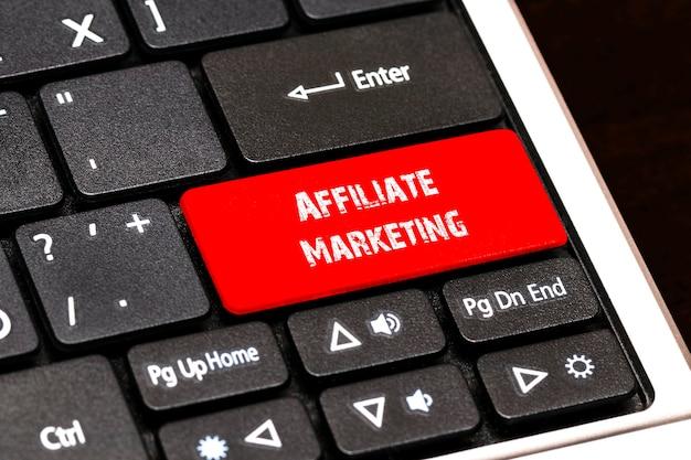 Na klawiaturze laptopa czerwony przycisk z napisem affiliate marketing.
