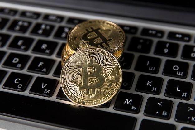Na klawiaturze laptopa leżą złote bitcoiny