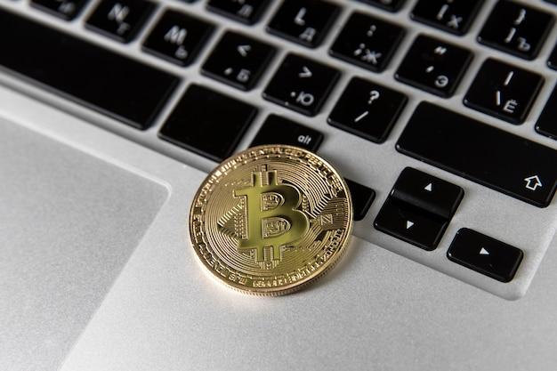 Na klawiaturze laptopa leży złoty bitcoin