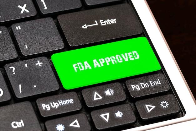 Na klawiaturze laptopa zielony przycisk z napisem fda approved.