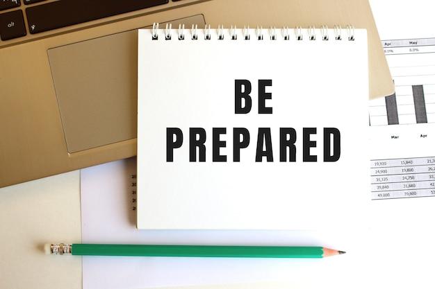 Na klawiaturze laptopa znajduje się notatnik z napisem be prepared.