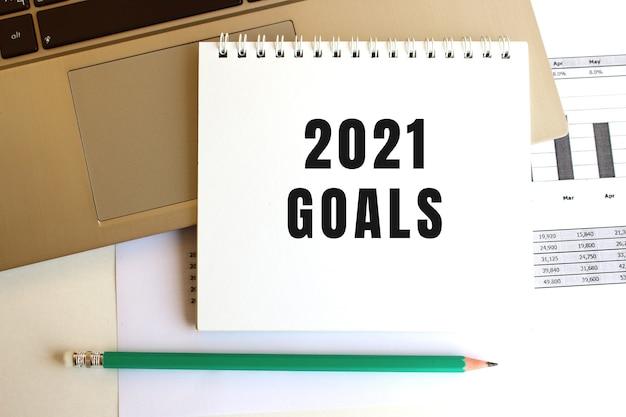 Na klawiaturze laptopa znajduje się notatnik z napisem goals 2021. minimalna przestrzeń do pracy.