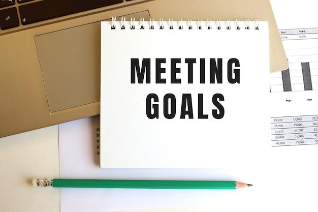 Na klawiaturze laptopa znajduje się notatnik z napisem meeting goals. minimalna przestrzeń do pracy.