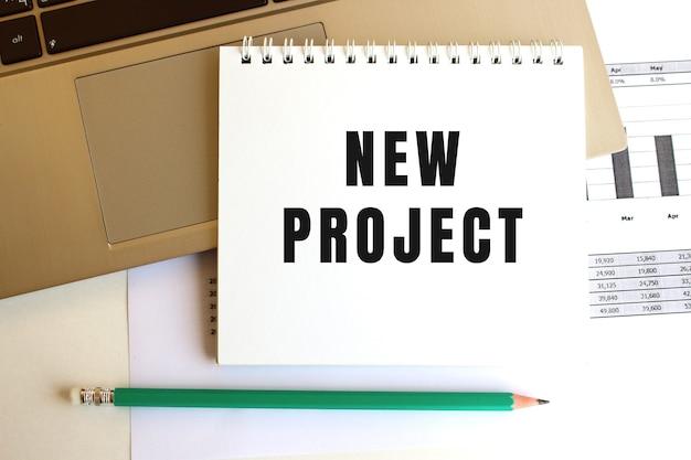 Na klawiaturze laptopa znajduje się notatnik z napisem new project