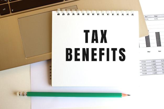 Na klawiaturze laptopa znajduje się notatnik z napisem tax benefits. minimalna przestrzeń do pracy.