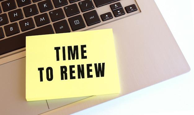 Na klawiaturze laptopa znajduje się notatnik z napisem time to renew. minimalna przestrzeń do pracy.