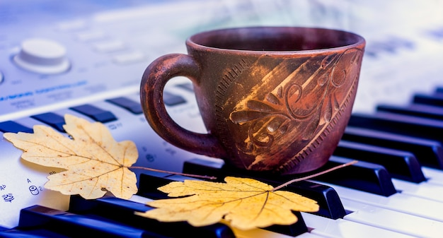 Na klawiszach fortepianu znajduje się kubek z żółtymi jesiennymi liśćmi klonu. nadeszła jesień. koncert jesienny
