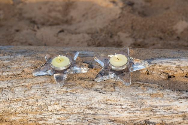 Na kłodzie na piasku są dwa świeczniki z świecą w kształcie gwiazdy