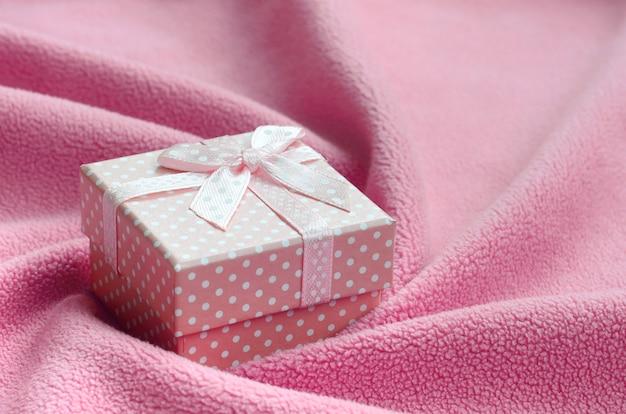 Na kocu leży małe pudełko w kolorze różowym z małą kokardką