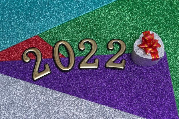 Na kolorowym jasnym błyszczącym tle nowego roku srebrne pudełko z czerwoną kokardą i złotymi cyframi 2022. koncepcja karty noworocznej.
