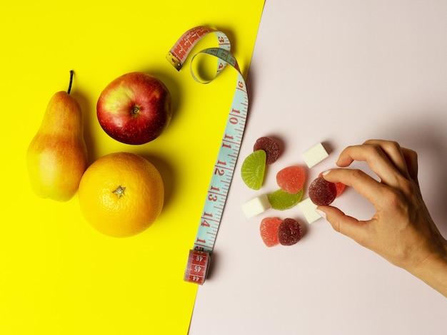 Na kolorowym tle ułożone są przydatne owoce i słodycze z różnych stron. w środku znajduje się taśma miernicza. kobieca ręka zabiera słodycz. pojęcie diety i wybór w żywieniu