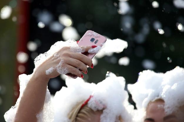 Na koncercie ludzie robią sobie selfie telefonem komórkowym w piance mydlanej