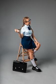 Na krześle siedzi uczennica, obok stoi tornister. izolacja na szarym tle