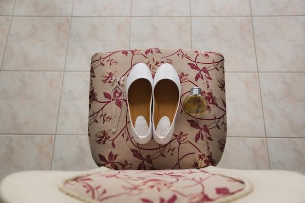 Na krześle stoją buty panny młodej z kryształkami