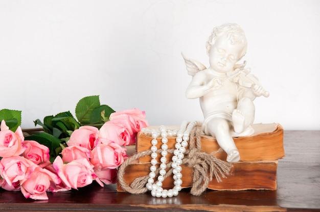 Na księdze siedzi figurka anioła grającego na skrzypcach.