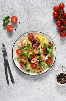Na kuchennym stole wymieszaj sałatkę z pomidorami i grillowanymi krewetkami z sosem i powojnikiem. widok z góry. betonowe tło żywności.