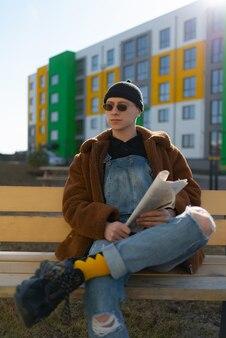 Na ławce na ulicy siedzi mężczyzna w okularach przeciwsłonecznych