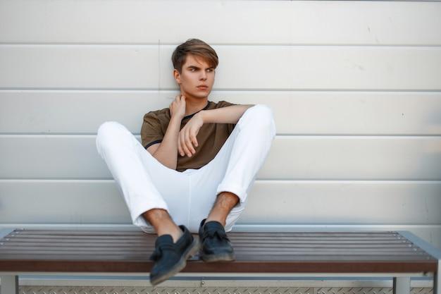 Na ławce odpoczywa modny mężczyzna w klasycznej koszulce i białych stylowych spodniach z czarnymi butami