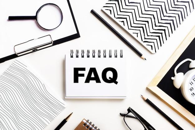 Na lekkim stole leżą zeszyty, lupa, budzik, okulary i długopis. a w środku znajduje się notatnik z tekstem faq często zadawane pytania