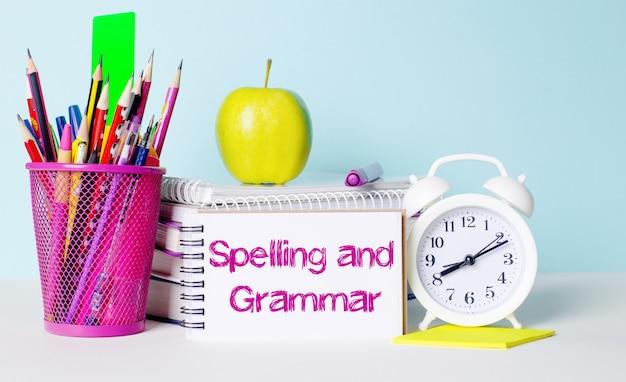 Na lekkim stoliku znajdują się książki, artykuły papiernicze, biały budzik, jabłko. obok znajduje się zeszyt z napisem pisownia i gramatyka. koncepcja edukacyjna.