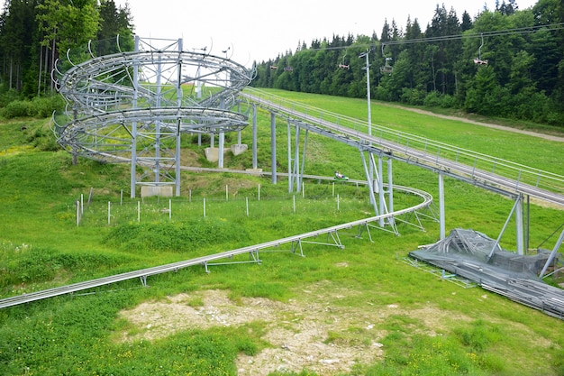 Na letnim zboczu góry budowa atrakcji kolejki górskiej na tle zielonej trawy. po prawej jest wyciąg narciarski
