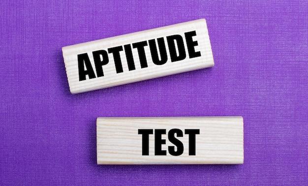Na liliowej jasnej powierzchni, jasne drewniane klocki z napisem aptitude test