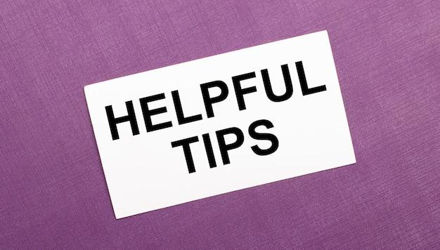 Na liliowej powierzchni biała kartka z napisem helpful tips