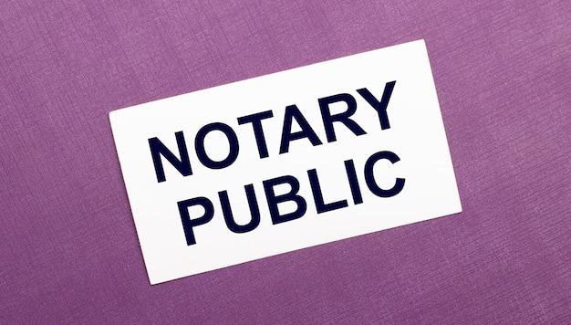 Na liliowym tle biała kartka z napisem notary public.