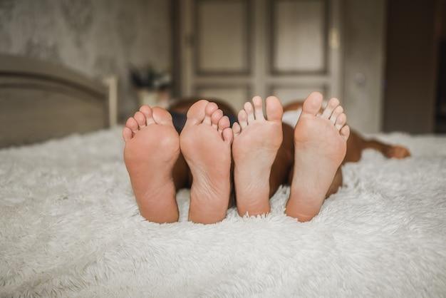 Na łóżku leżą dorosły mężczyzna i kobieta z bosymi stopami