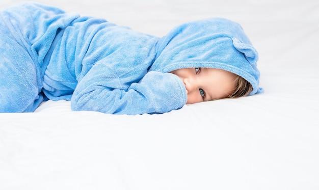 Na łóżku leży dziecko w szlafroku. dziecko w niebieskim ręczniku na białym prześcieradle