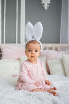 Na łóżku w pokoju siedzi dziewczynka w różowej sukience i opasce z uszami zająca