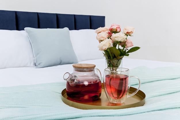 Na łóżku w sypialni taca z przezroczystym czajniczkiem, kubek i wazon z różami