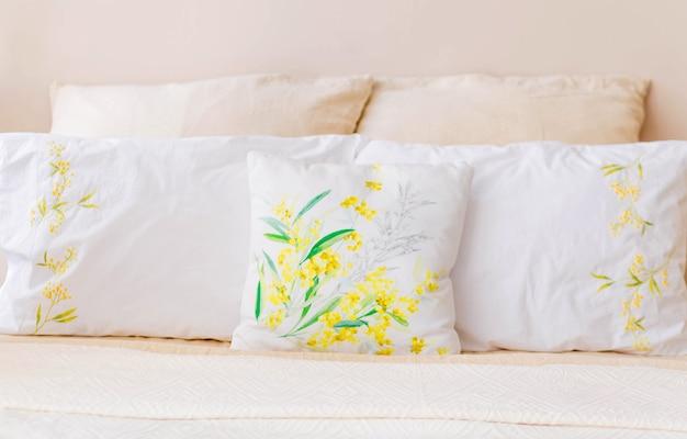Na łóżku znajduje się wiele poduszek w kolorze białym i beżowym. poziome zdjęcie