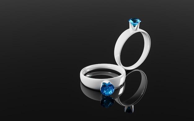 Na lustrzanej powierzchni odbijają się dwa pierścionki z białego złota z niebieskimi lub niebieskimi diamentami.