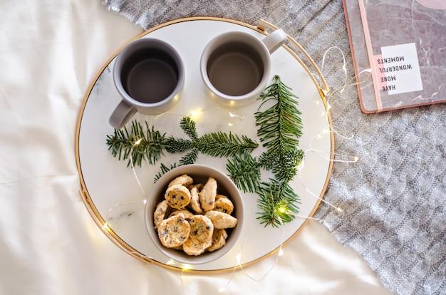 Na marmurowej tacy ze złotym brzegiem stoją dwie szare filiżanki herbaty i czekoladowe pierniczki. gratka dla świętego mikołaja. gałąź choinki z girlandami zdobią kartkę noworoczną. skopiuj miejsce