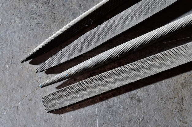 Na metalowej powierzchni znajduje się kilka metalowych pilników. zbliżenie.