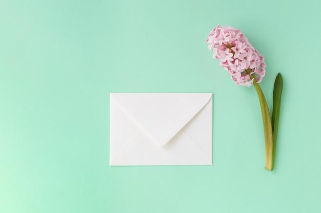 Na miętowo zielonym tle znajduje się biała koperta i różowy kwiat hiacyntu.