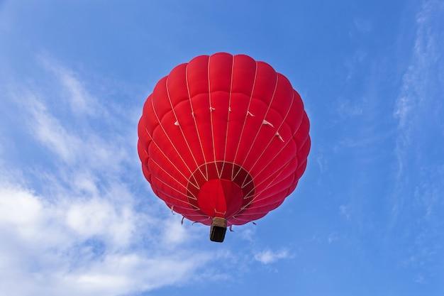Na niebie leci czerwony balon. na ziemi leży balon z koszem, sprzęt do napełniania balonu zimnym i gorącym powietrzem. przygotowanie balonu do startu.