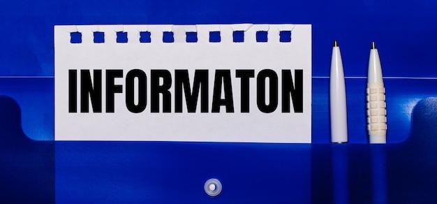 Na niebieskiej powierzchni białe długopisy i kartka papieru z napisem informacja