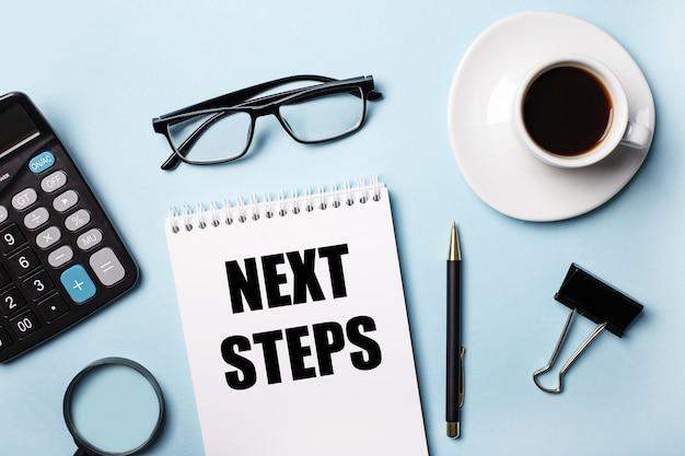 Na niebieskiej ścianie okulary, kalkulator, kawa, lupa, długopis i notatnik z napisem następne kroki