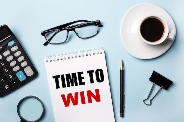 Na niebieskiej ścianie okulary, kalkulator, kawa, lupa, długopis i notatnik z napisem time to win