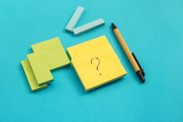 Na niebieskiej ścianie umieszczone są naklejki o różnych rozmiarach i kolorach. obok jest długopis. notesy na notatki i przypomnienia. na liściu jest napisany znak zapytania.